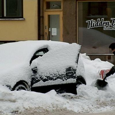 Mies kaivaa autoa kinoksesta