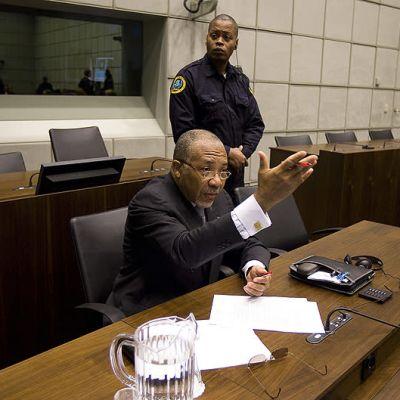 man håller upp handen och pratar i en rättssal.