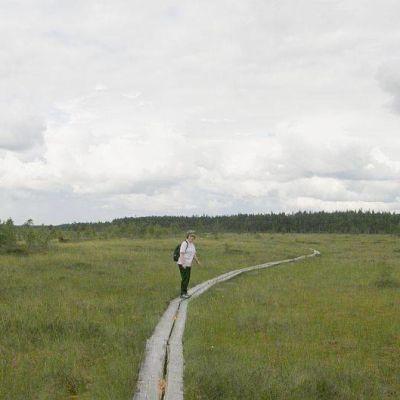 Retkeilijä kävelee pitkospuilla Torronsuolla.