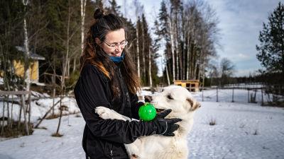 En kvinna kramar sin hund som står på två ben.