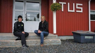 Två kvinnor sitter på trappan till en röd träbyggnad.
