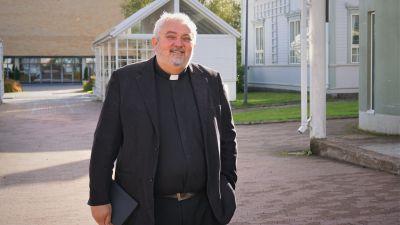 Man i svart kostym och prästkrage står på en innergård.