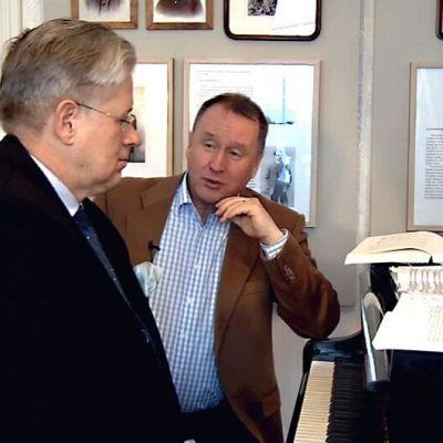 Kaksi miestä istuu pianon ääressä.