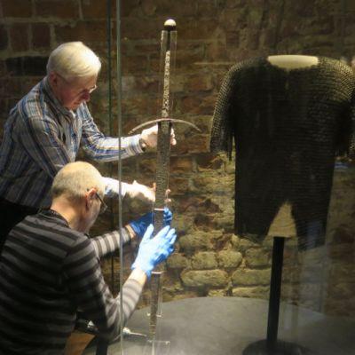 Kaksi miestä asettelee miekkaa vitriiniin
