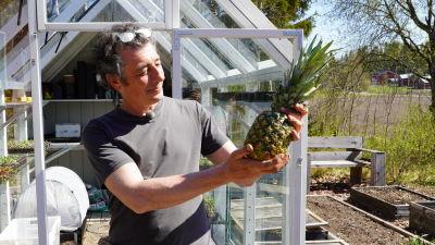 En man med en ananas i handen framför ett växthus.