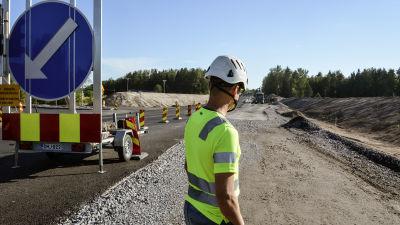Man i arbetskläder och skyddshjälm står vid vägbygge.