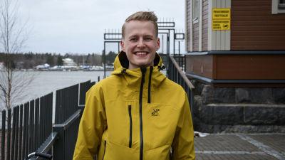 Ung man i gul jacka står utomhus, tittar leendes in i kameran. I bakgrunden syns vatten.