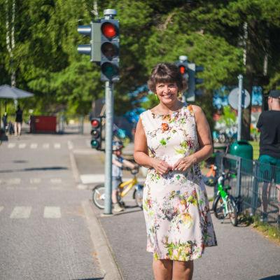 En glad kvinna står på en asfalterad gångbana. I bakgrunden syns ett barn på en cykel och ett rött trafikljus.