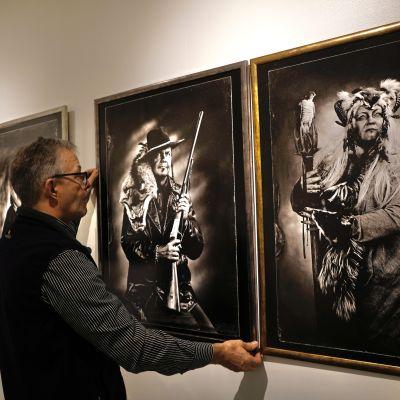 Pekka Homanen asettelee kehystettyä valokuvaa seinälle Kainuun museossa.
