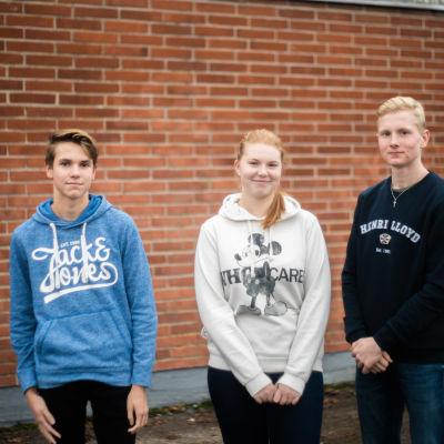 Tre studerande står framför en tegelvägg. Samuel Berg (t.v.), Rebecca Sandfors och Robin Forsman.