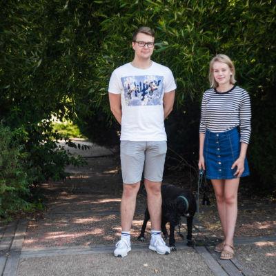 Niklas Matikainen (t.v.) och Matilda Saarinen poserar framför en buske tillsammans med hunden Ricco. De ser glada ut.