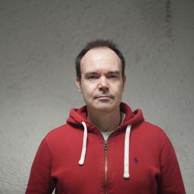 En man med allvarlig min står framför en vit vägg. Han är iklädd en röd munkjacka.