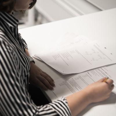 En kvinna skriver ett inträdesprov. Man ser inte kvinnans ansikte.