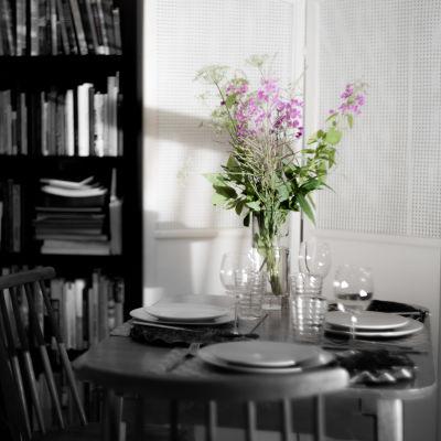 En bukett blommor på ett bord med en enkel festdukning. Endast blommorna har färg i bilden, allt annat är svartvitt.
