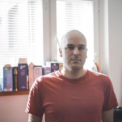 En allvarlig man står i ett kök. Solen lyser in genom fönstret bakom honom.