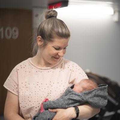 En kvinna håller ett spädbarn i famnen. Hon ser på barnet. I bakgrunden syns ballonger.