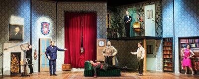 En teaterscenografi av en ståtlig salong, i fonden ett väldigt fönster med långa röda sammetsgardiner. I mitten en divan och på divanen ligger en man i rökrock orörlig. Omkring honom står sex andra skådespelare som tittar på honom.