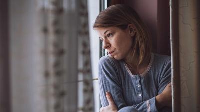 Kvinna tittar ut genom fönstret