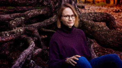 Författaren Maria Grundvall sitter i skogen.