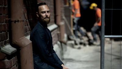 Ilmari Käihkö. En svartklädd man lutar mot en tegelvägg. Bilden är mörk och han har en allvarlig min. Mannen har kort ljusbrunt hår och skägg.