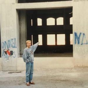 Nuori mies osoittaa sormellaan keskeneräistä rakennusta. Sen seiniin on spreijattu graffiteja. Pojalla on jalassaan sandaalit.