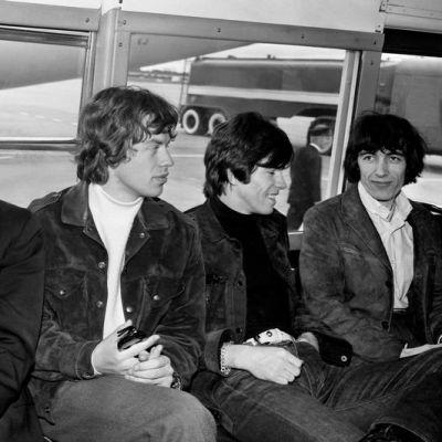 The Rolling Stones -yhtyeen jäsenet istuvat lentokenttäbussissa.