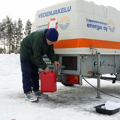 Mies ottaa vettä kanisteriin vedenjakelupisteellä.