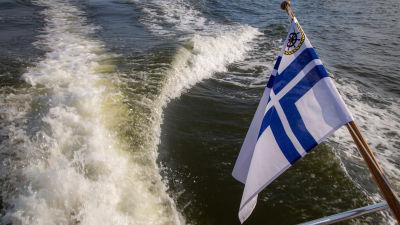 Aktern på en motorbåt med finsk klubbflagga.