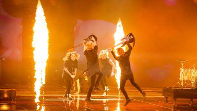 Blind Channel uppträder på eurovisionsscenen. De hoppar i en ring med elgitarrerna höjda och eldpelare runt dem.