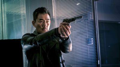Skurken (Richie Jen) står med draget vapen och ser bister ut.