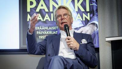Björn Wahlroos sitter på en scen och talar i en mikrofon.