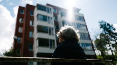 Kvinnlig pensionär på bänk utanför ett höghus.