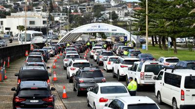 Bilar som köar till en drive-in coronavaccineringsstation i Sydney.