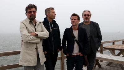 De fyra medlemmarna i Bo Kaspers Orkester står uppställda fram för ett dimmigt hav.