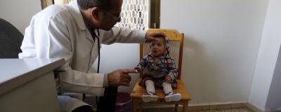 Ett litet barn med ett sår i ansiktet undersöks av en läkare på en mottagning.