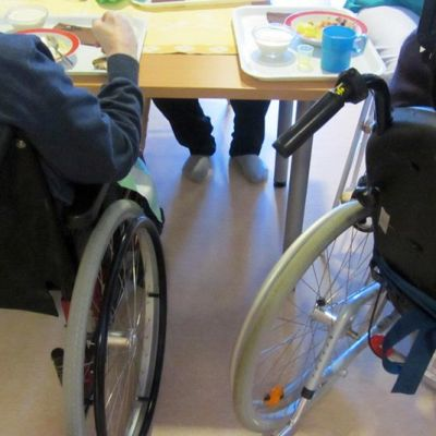 Vanhukset pyörätuoleissa ruokailemassa.