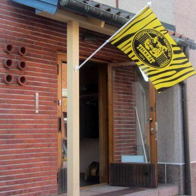 Kuvassa Kokkolan Tiikreiden lippu oven pielessä.