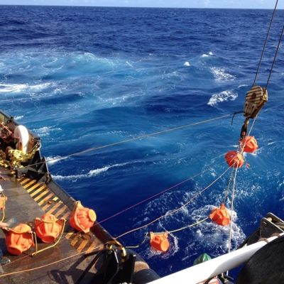 Tutkijat kiskovat tutkimuslaitetta vinssillä laivan kannelle merestä.