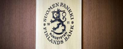 Finlands Banks logo mot en trävägg.