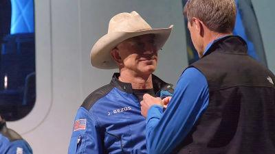 Jeff Bezos får ett astronautmärke fäst på kragen.