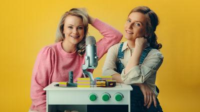 Carro och Rebecka sitter bakom en leksaksugn mot en gul bakgrund och ser in i kameran.