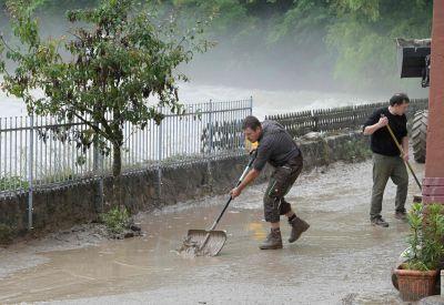 Två personer skottar bort lera efter översvämningen i Marktschellenberg i Tyskland.