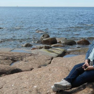 Merja Naroma istuu rantakalliolla Kirkonmaan eteläkärjessä taustanaan Itäinen Suomenlahti.