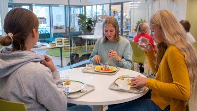 Tre flickor sitter vid ett runtbord i Vårberga skolas matsal och äter skollunch.