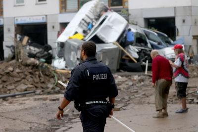 En polis går på en lerig väg i en stadsskärna. Framför honom finns en hög med flera bilar. I bakgrunden syns ett äldre par. Mannen är framåtlutad och kvinnan håller sin hand på hans rygg.