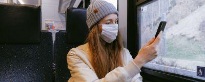 Kvinna i grå mössa och beige jacka och munskydd åker tåg, tittar på sin mobiltelefon.