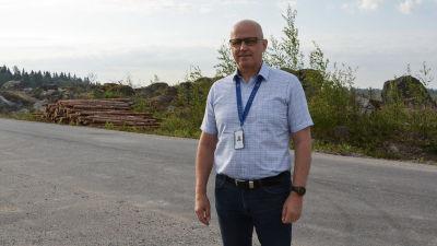 Medelålders man i kortärmad skjorta står på en asfalterad väg med ett kalhygge i bakgrunden.