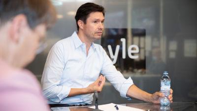Charly Salonius-Pasternak gästar Yles studio. Han har kort brunt hår och en blå skjorta. Han sitter vid ett bord. I ena handen håller han en vattenflaska och den andra gestikulerar, som om han är i mitten av en mening.