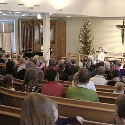 Kouluikäisiä ja vanhempia kirkossa.