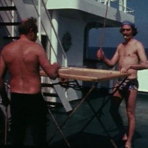 Merimiehet pelaavat laivankannella korona-lautapeliä.